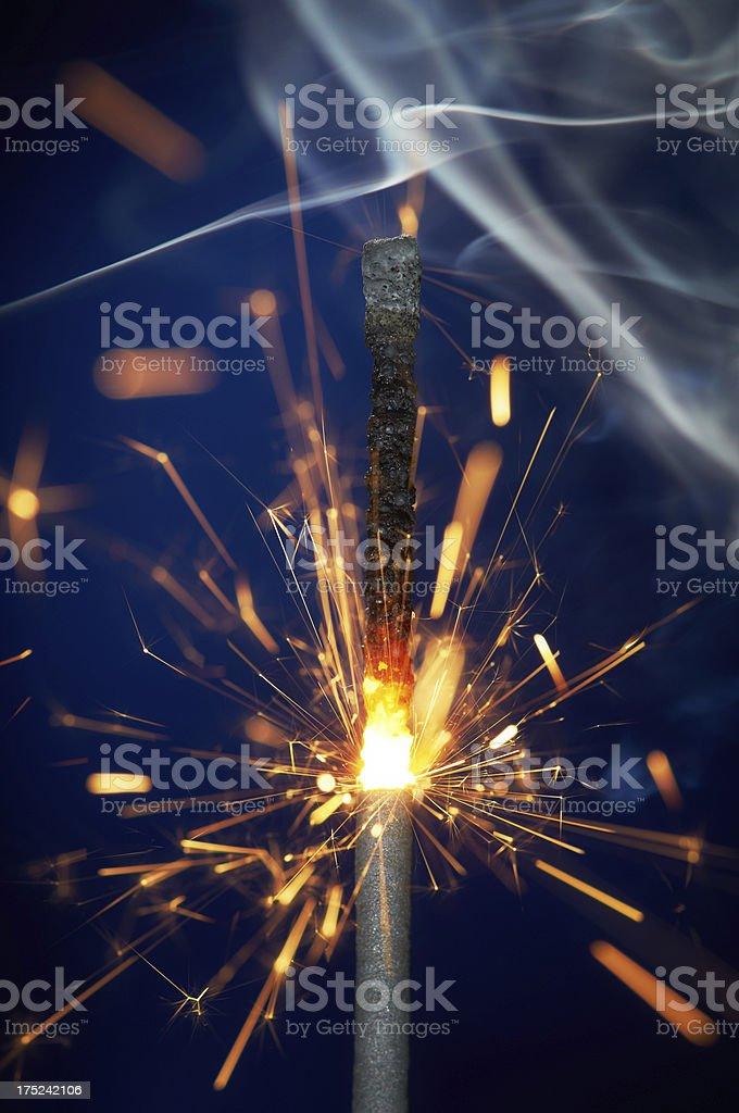 Sparkler on blue blurred background royalty-free stock photo