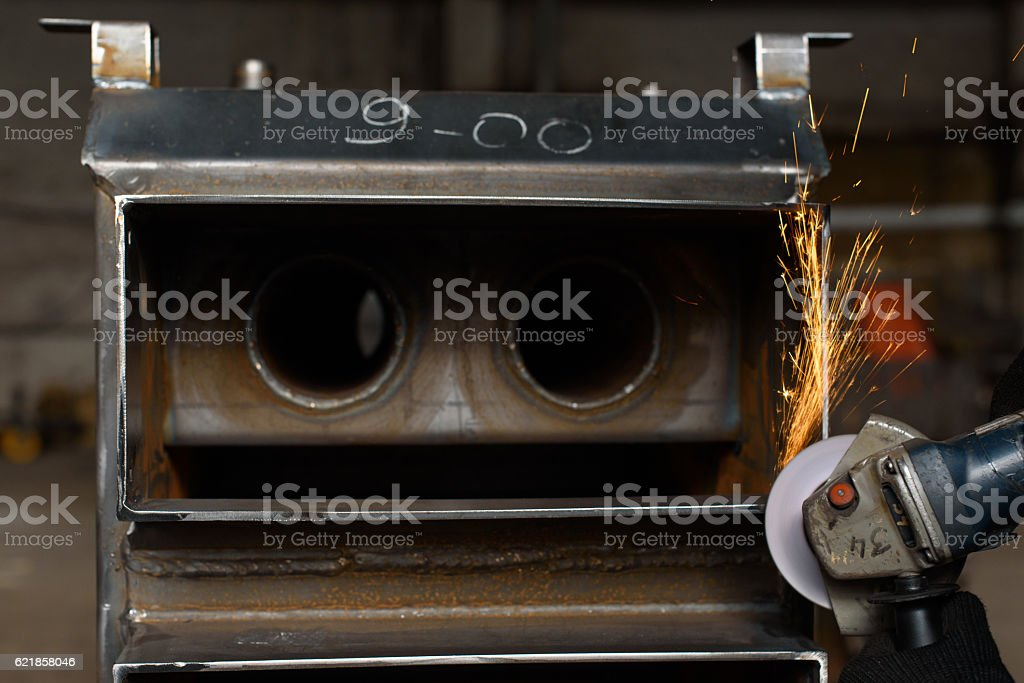 Sparkles of solder machine illuminate black solid fuel boiler stock photo