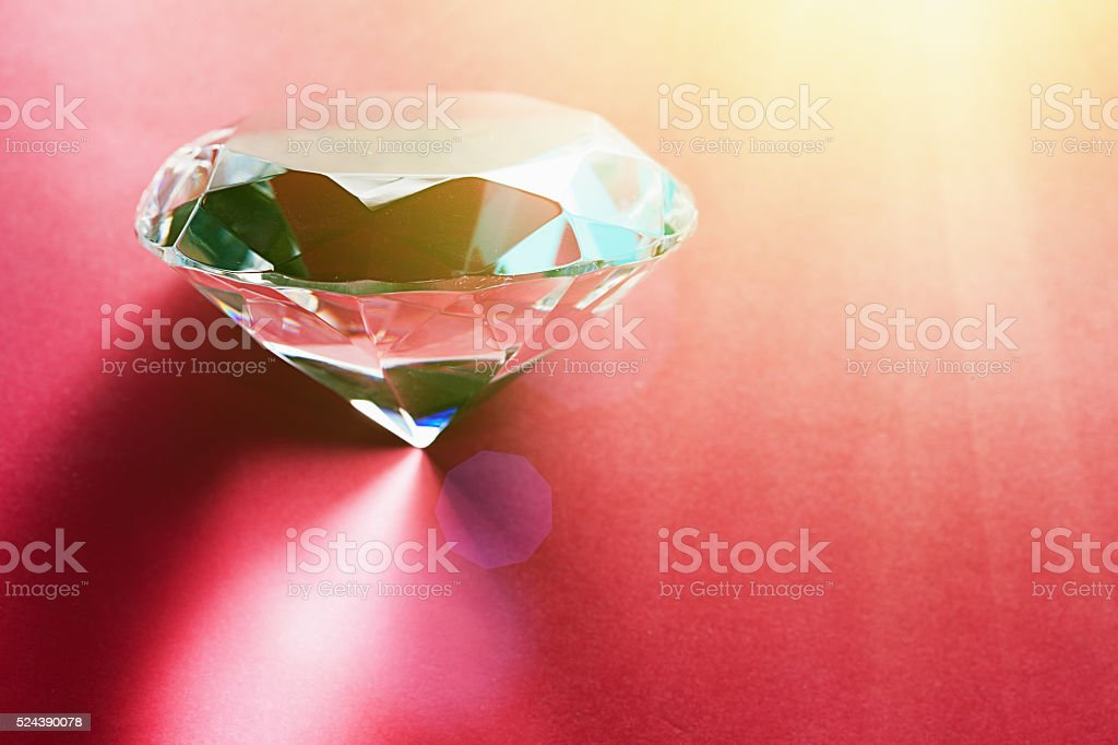 Sparkling faceted diamond-like crystal on red stock photo