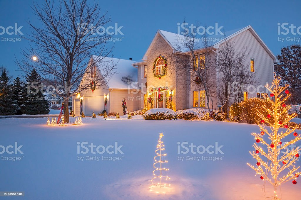 Sparkling holiday decorated home at evening with Christmas lighting, snow stock photo