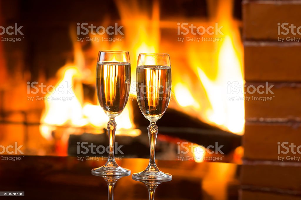 Sparkling wine in front of warm fireplace. Romantic, cozy atmosphere stock photo