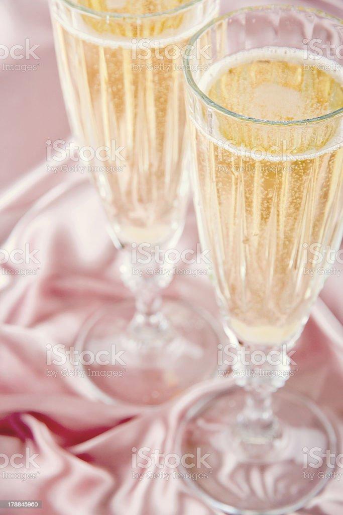 Sparkling wine on pink satin background royalty-free stock photo