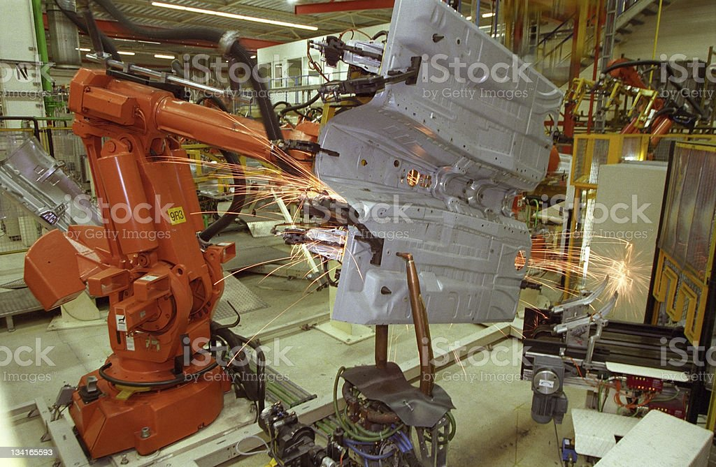 Sparks are flying from industrial welding robot at car factory royalty-free stock photo
