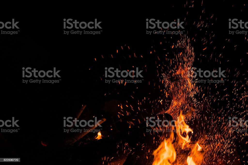 Sparks bounce off from a bonfire at night stock photo