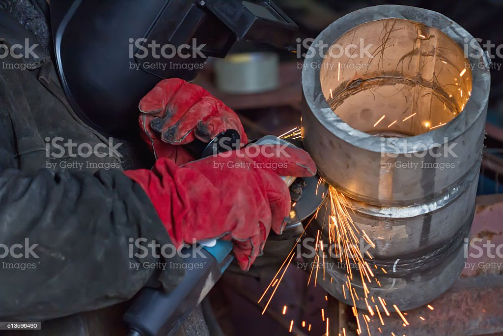 Sparks during machining of the weld stock photo
