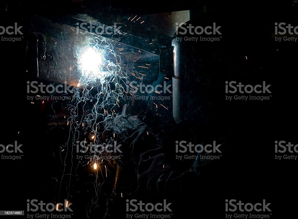 Sparks fly during welding in dark, confined space stock photo