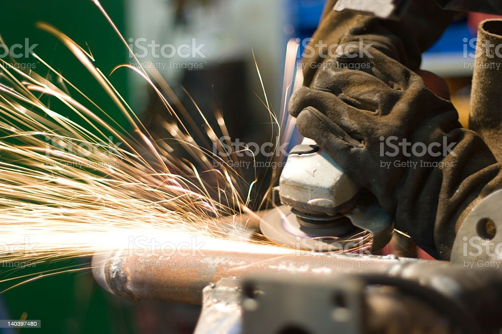 Sparks flying from worker grinding metal tubing royalty-free stock photo