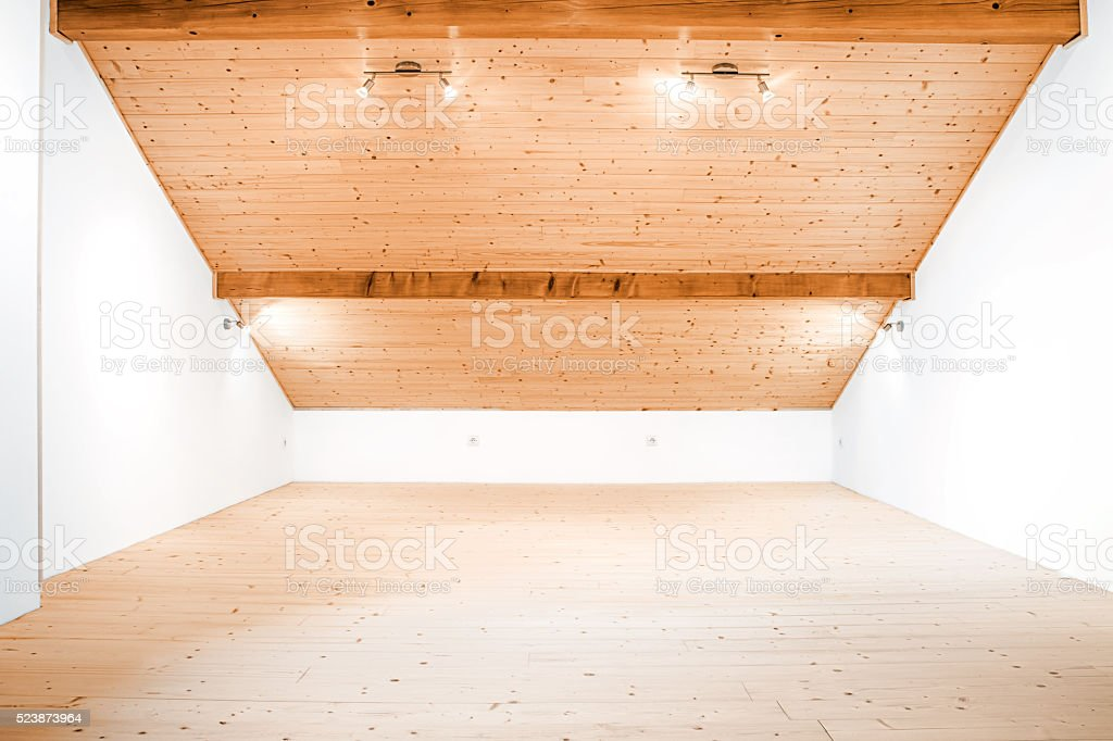 Sparse and bright empty wooden attic with white walls stock photo
