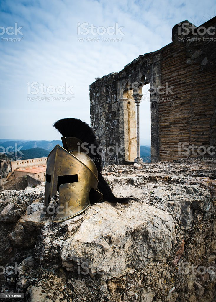 Spartan helmet on castle ruins. stock photo