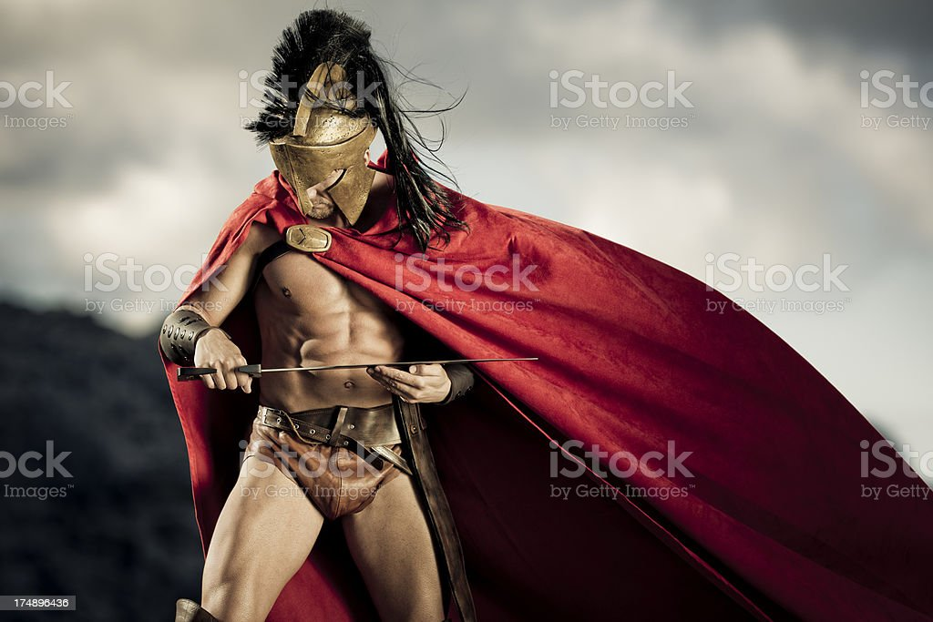 Spartan warrior looking at his sword stock photo