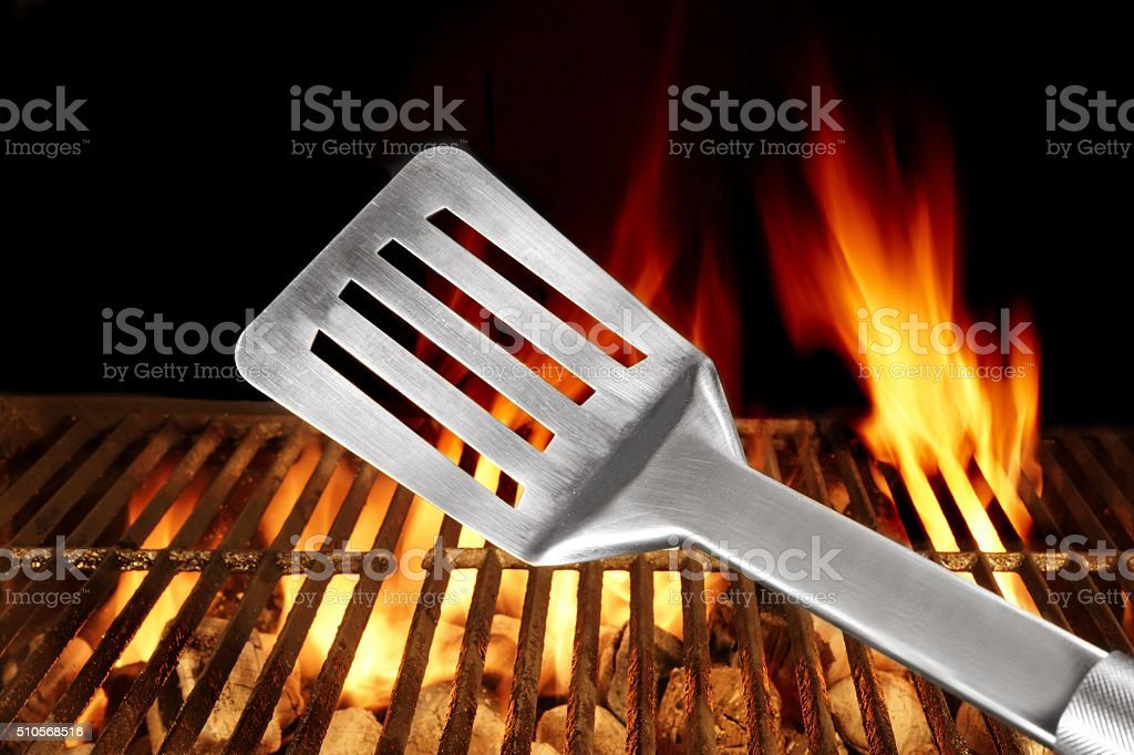 Spatula Close Up And Barbecue Flaming Grill On The Background stock photo