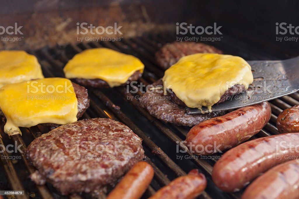 Spatula with Cheeseburger on grill stock photo