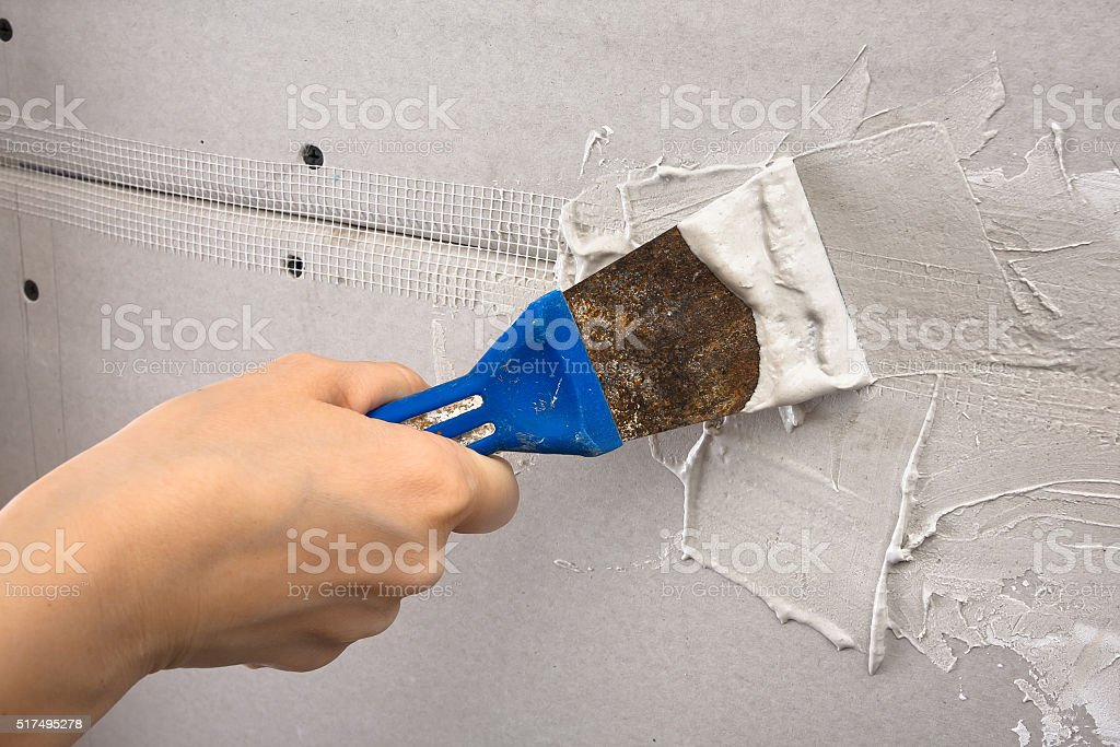 spatula with plaster in hand during plastering walls, closeup stock photo