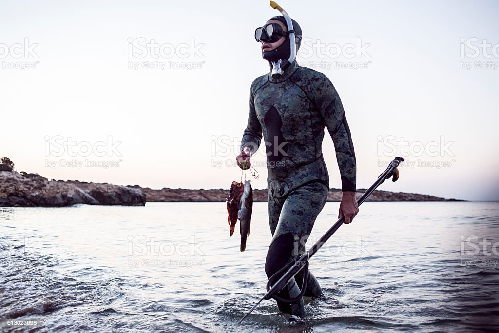 spear fisherman coming back from the sea stock photo