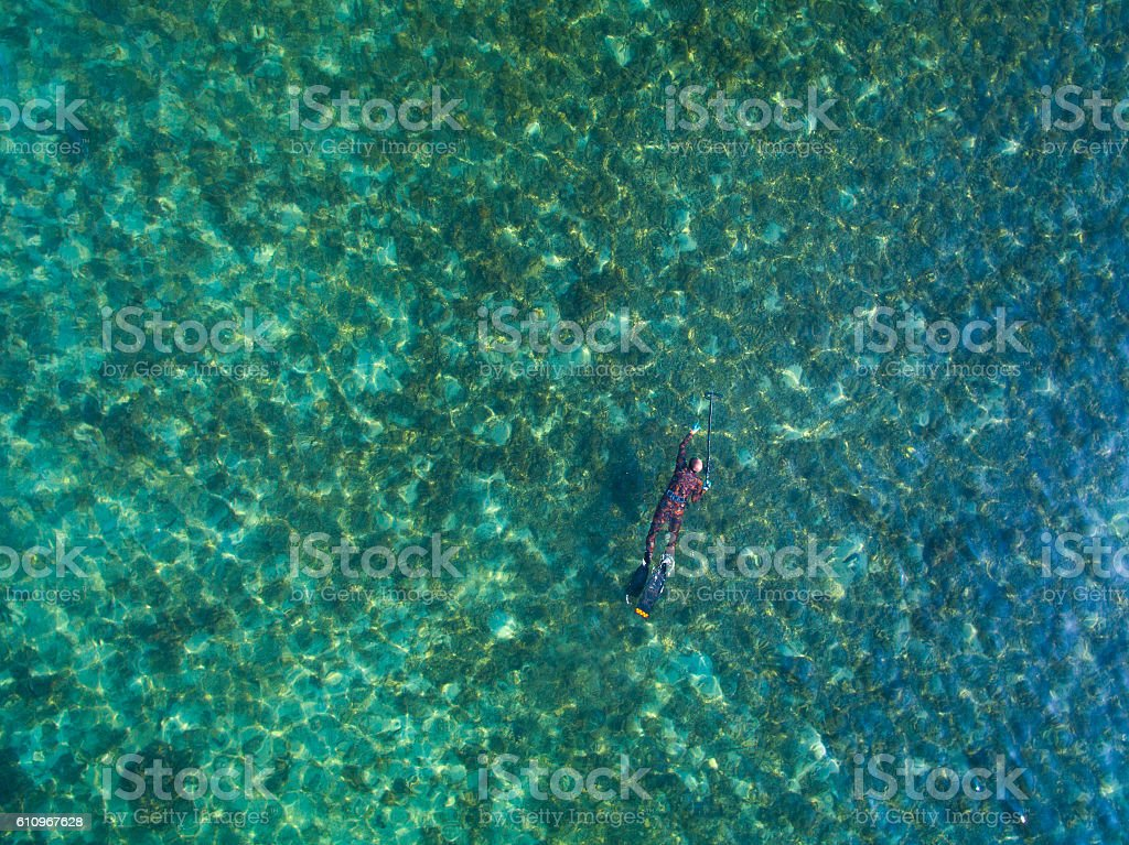 spearfishing freediver under water with a bird's-eye view stock photo