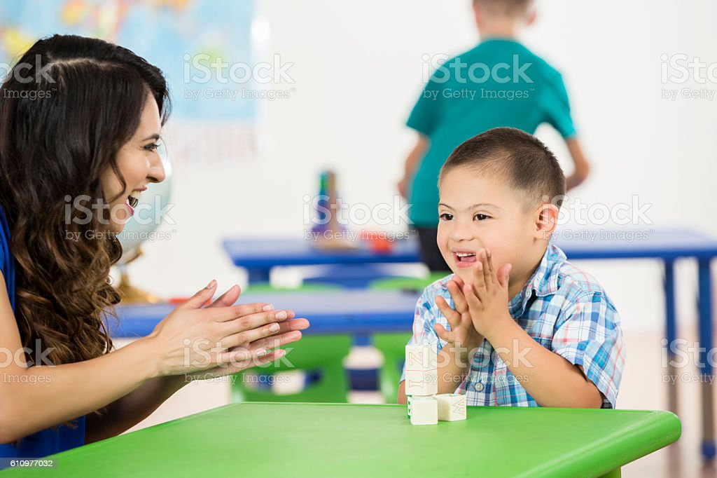 Special education teacher works with boy with Down's Syndrome stock photo