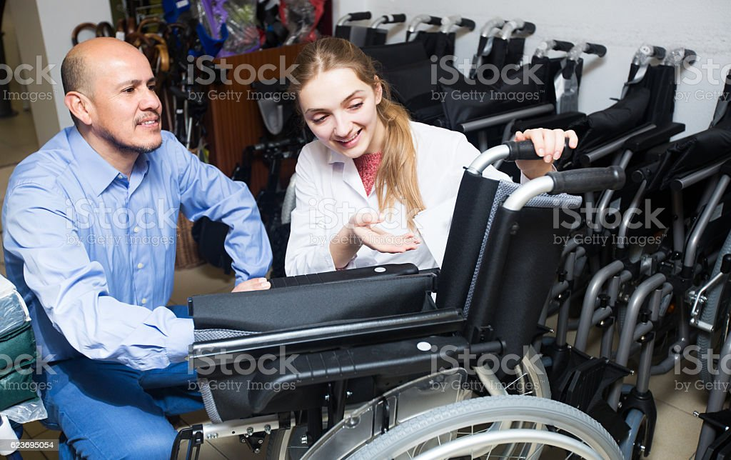 Specialist consulting client about wheelchairs stock photo