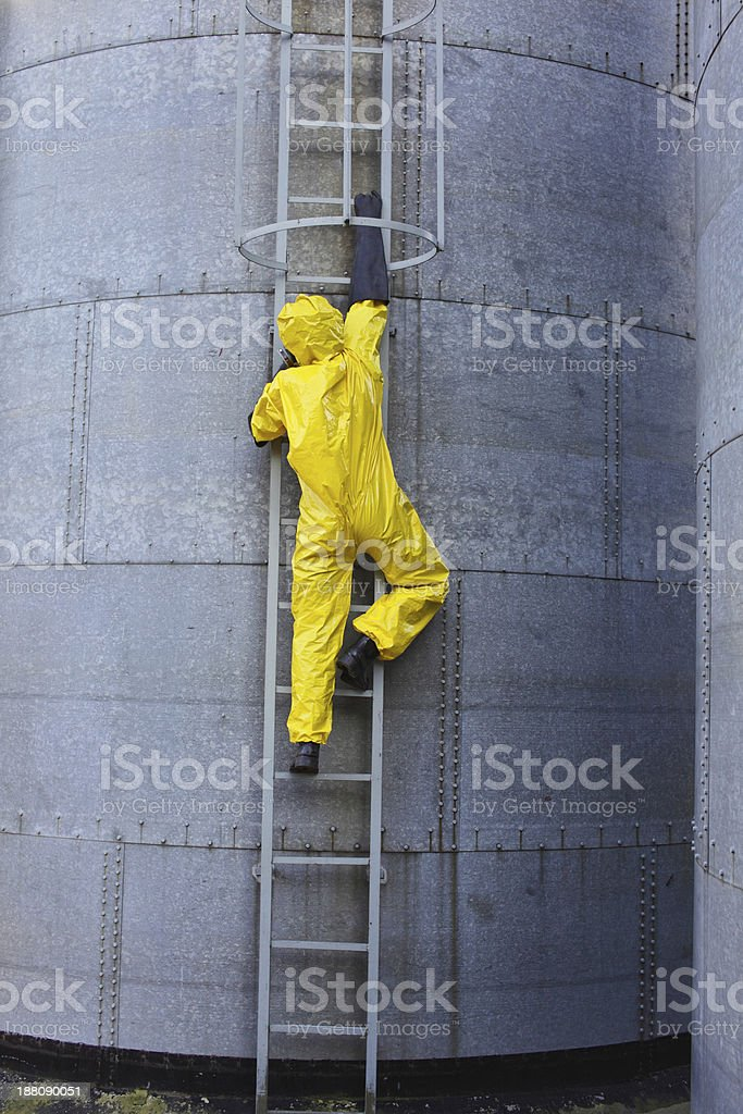 specialist in uniform going up a  ladder on storage tank stock photo
