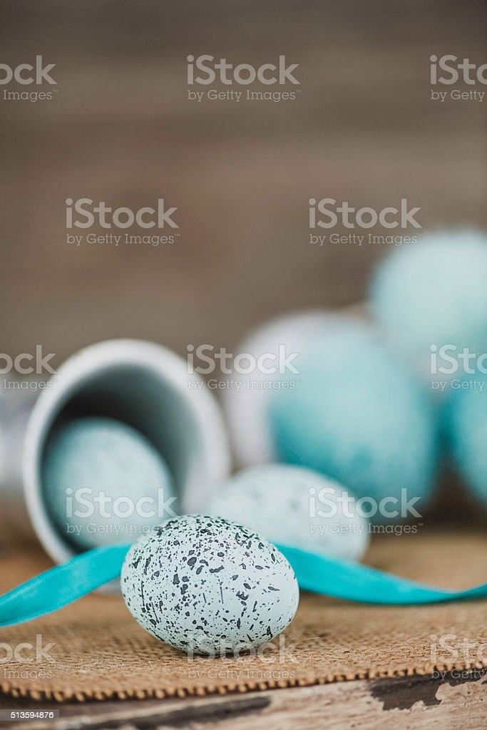 Speckled blue Easter eggs with ribbon. Rustic Easter still life. stock photo