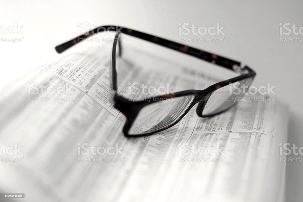Speckled Eyeglasses on a Folded Newspaper - Stock Quotes stock photo