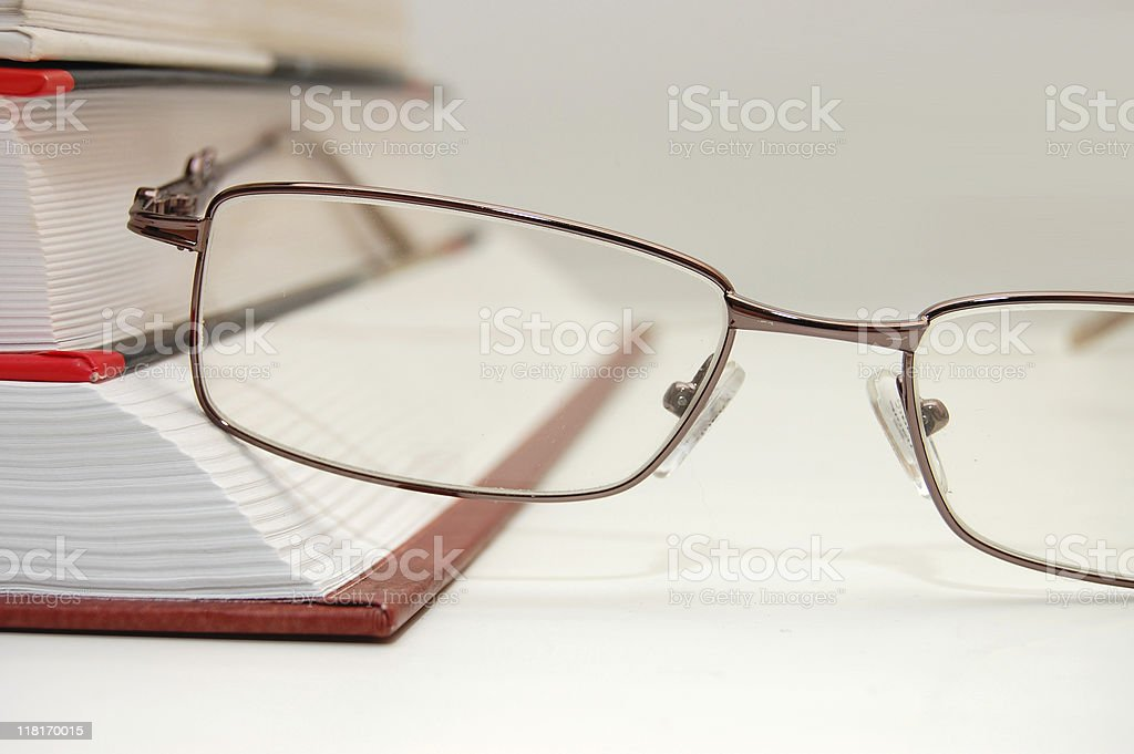 spectacles laying on the closed book stock photo