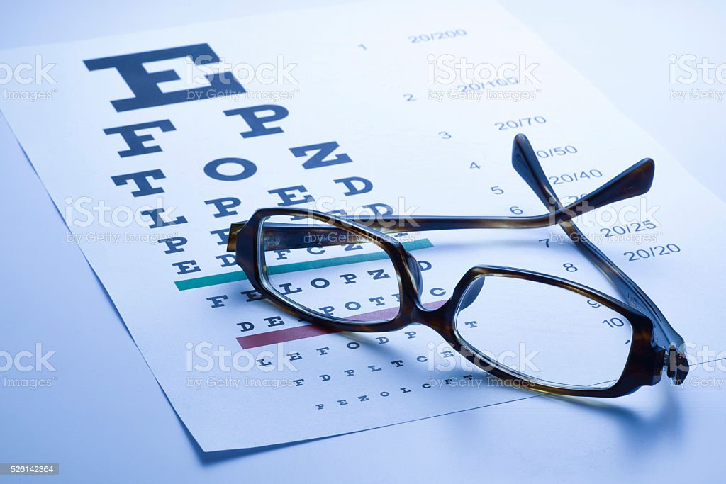 Spectacles with eye chart, blue tone stock photo