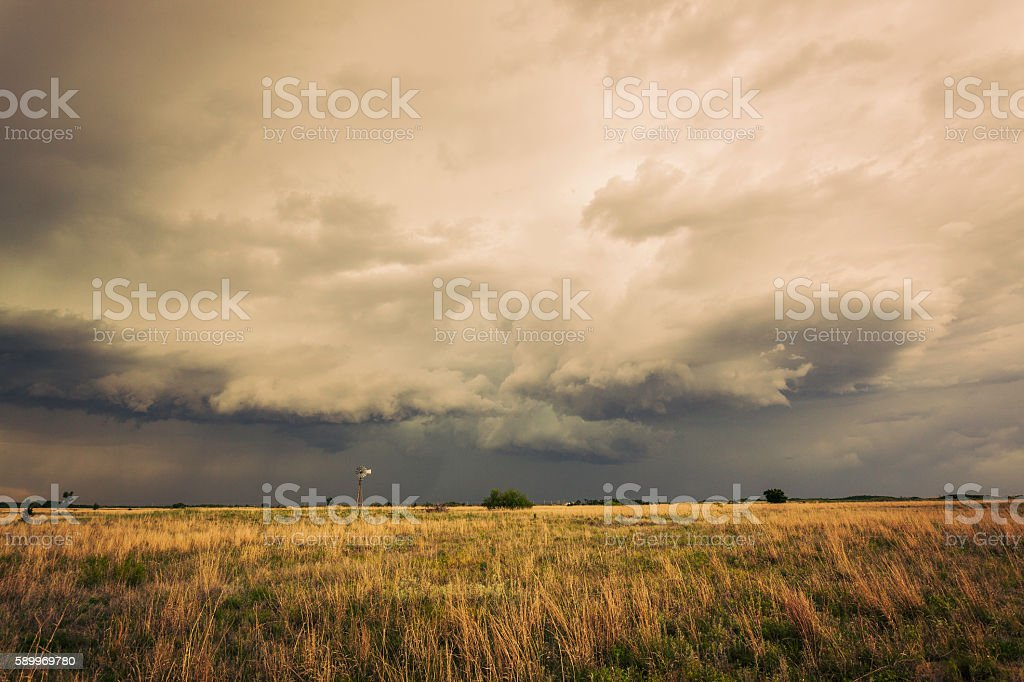 Spectacular storm clouds loom over lone windmill (windpump) stock photo