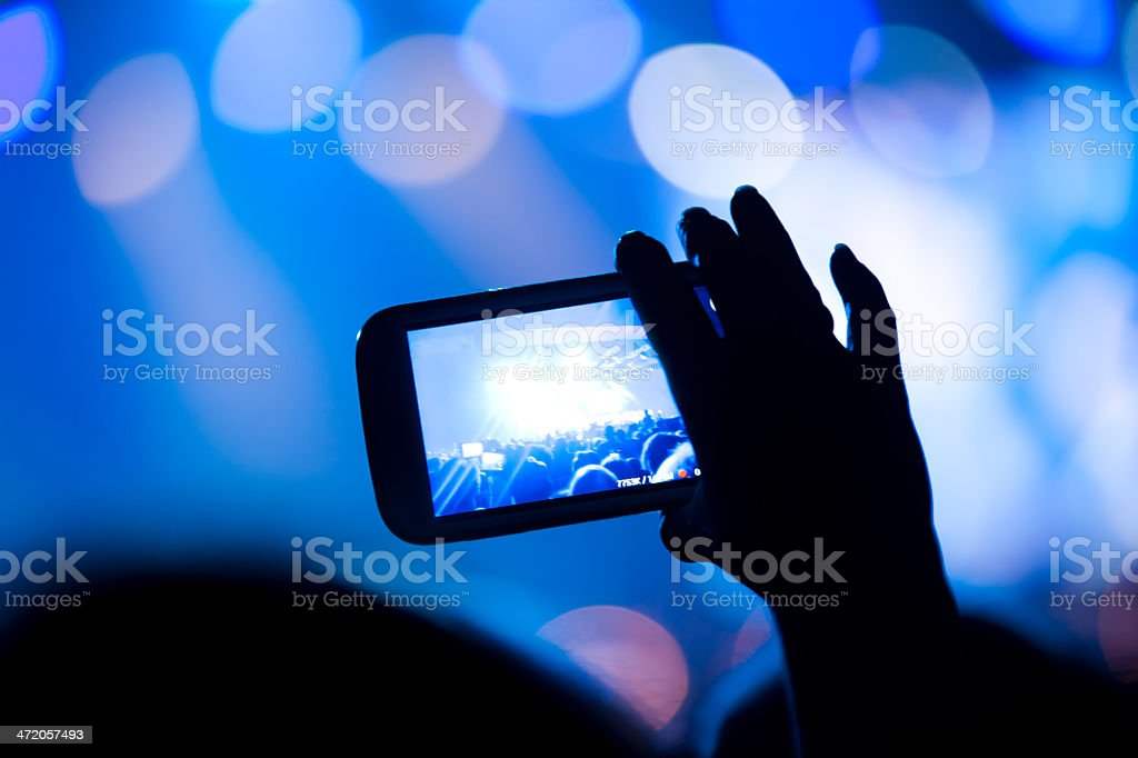 Spectator filming concert with his cell phone royalty-free stock photo
