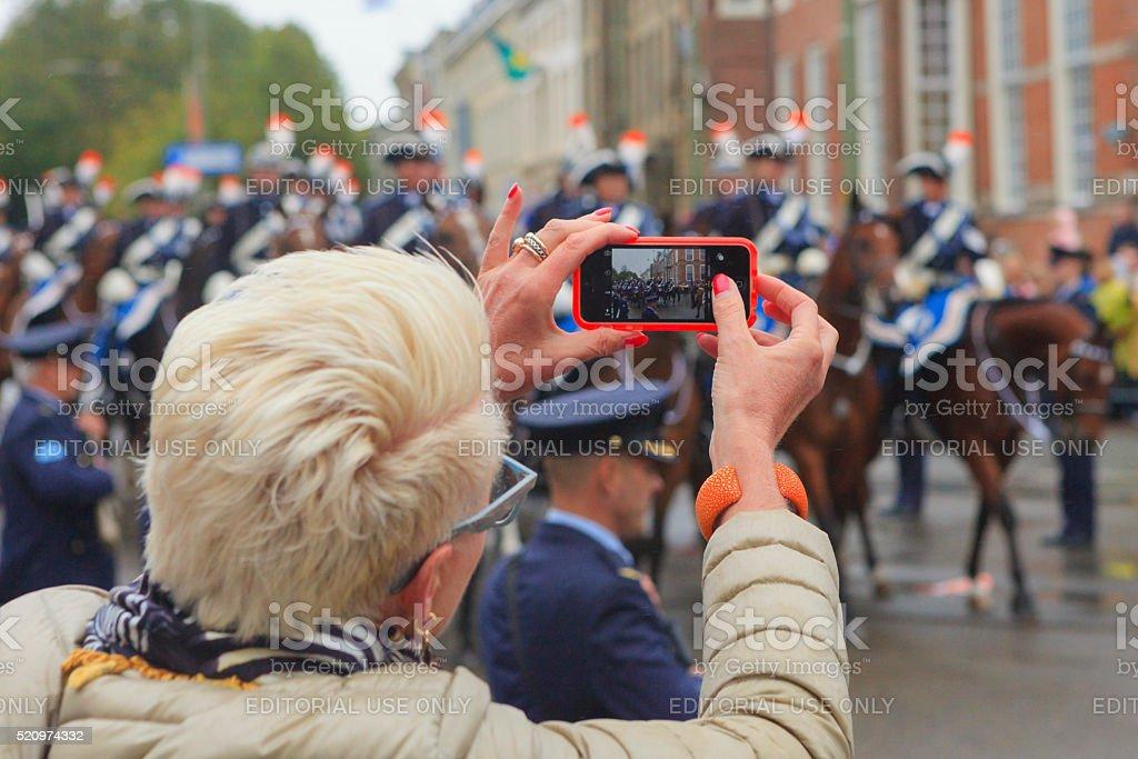 spectator photographing the royal parade on Lange Voorhout during Prinsjesdag stock photo
