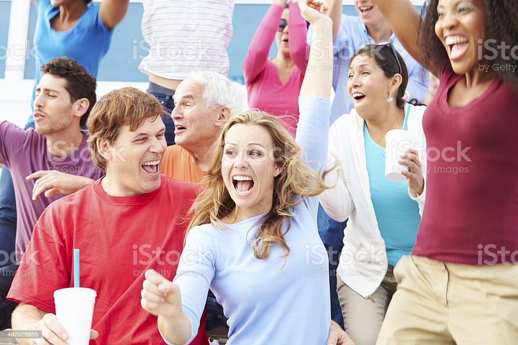Spectators Celebrating At Outdoor Sports Event stock photo
