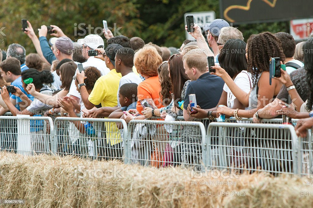 Spectators Use Their Smart Phones To Document Soap Box Derby stock photo