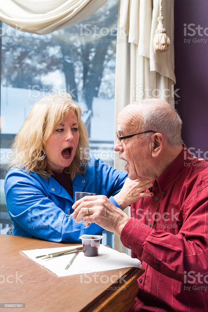 Speech therapist listens for dry voicing after swallowing stock photo