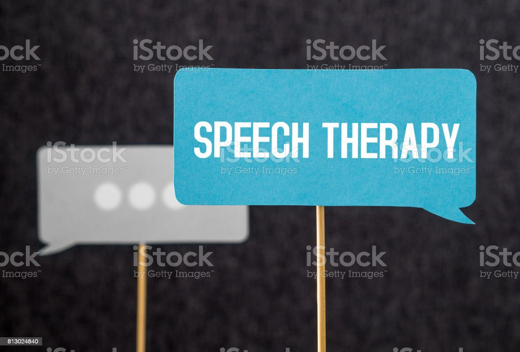Speech therapy text on cardboard speech balloon or bubble on wooden stick. Stuttering, lisp and learning to talk concept. stock photo