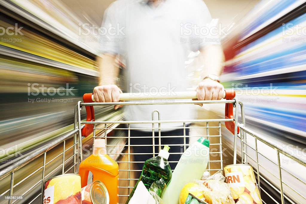 Speed blurs male shopper in supermarket with full shopping cart royalty-free stock photo