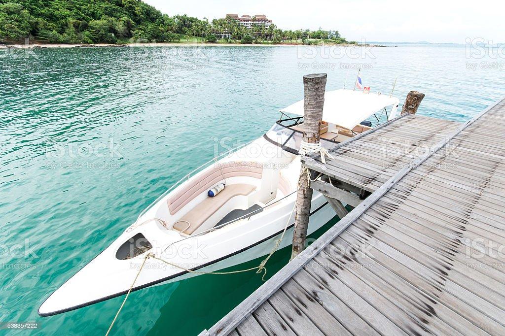 speed boat at blue sea near Wooded bridge stock photo