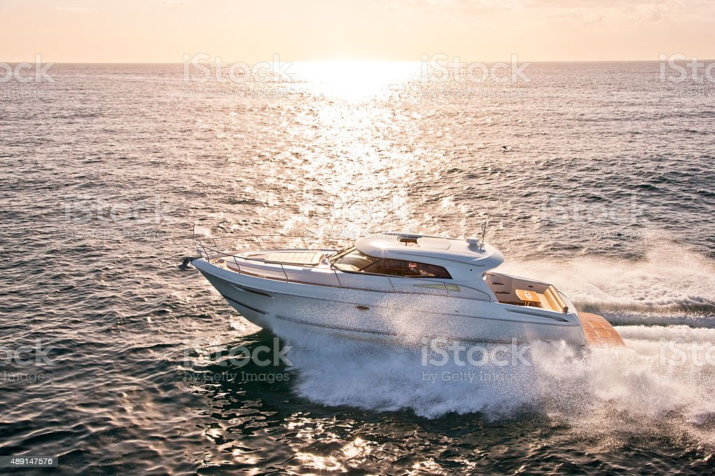 Speed boat in the ocean with sun setting behind stock photo
