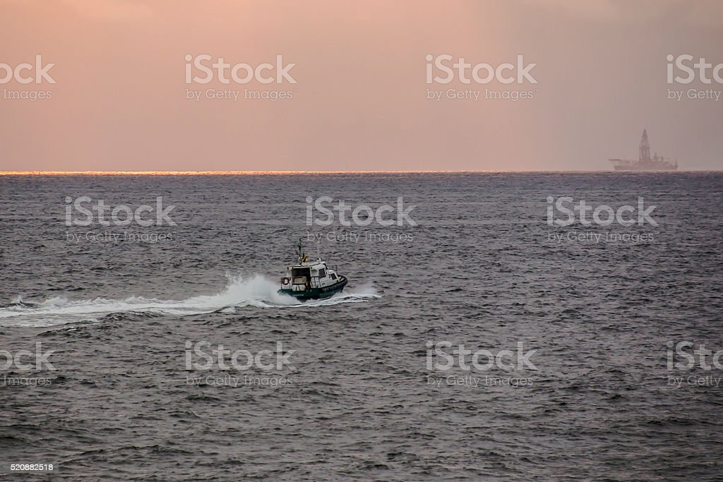 speed boat is sailing to the oil rig stock photo
