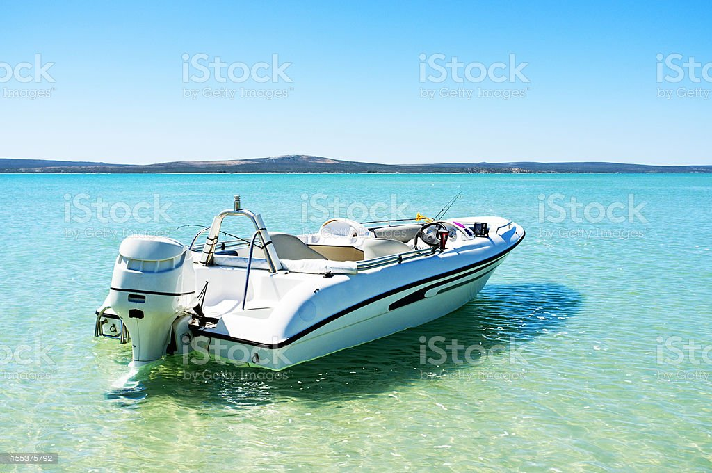 Speed boat moored in the shallows of turquoise lagoon stock photo