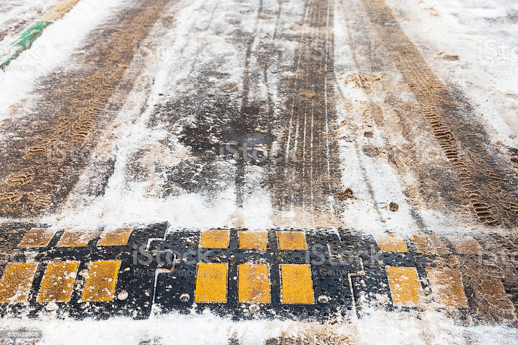 speed bump in snow on urban road in winter stock photo