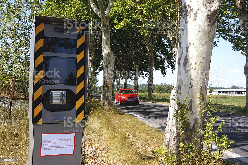 Speed camera on the side of a tree lined road stock photo