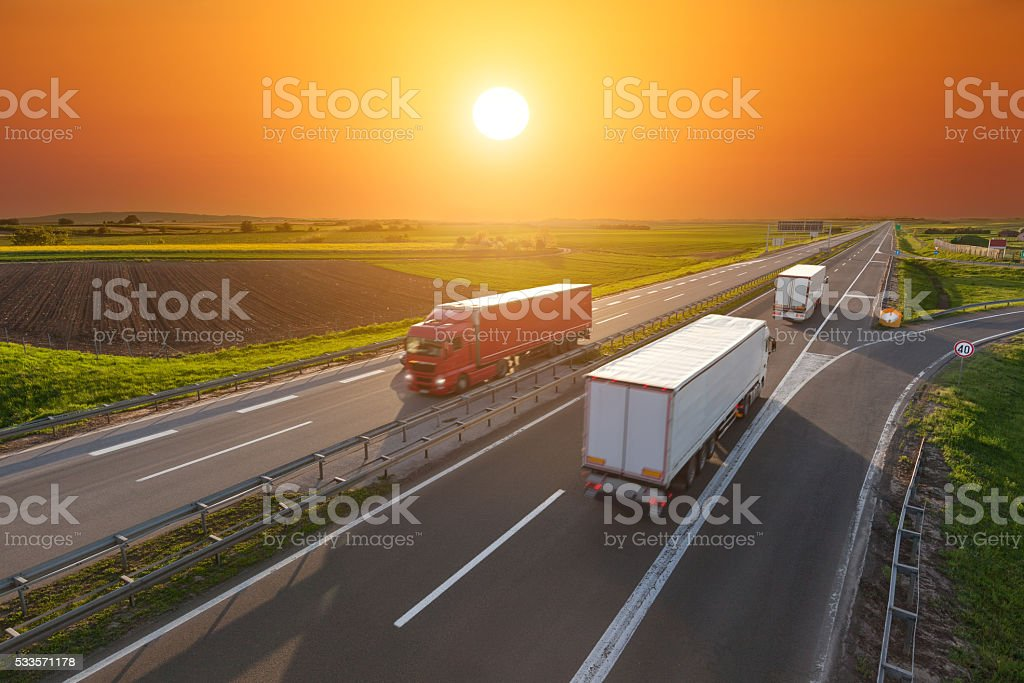 Speed delivery trucks on the empty highway at sunset stock photo