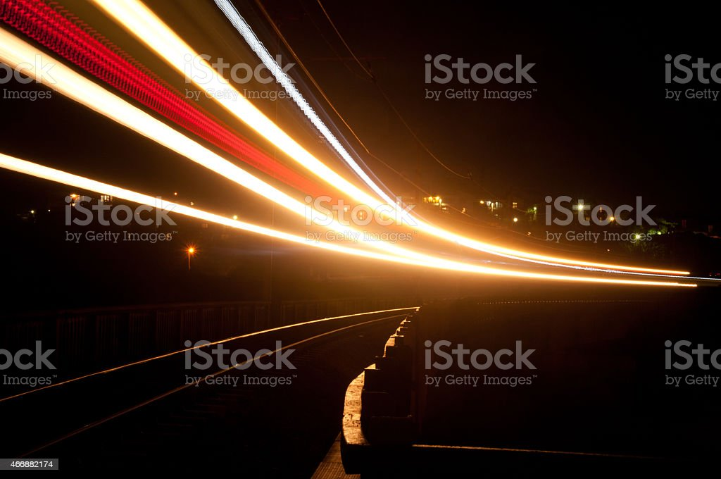 Speed light trail left by a train at night stock photo