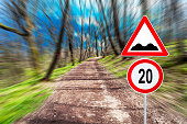 Speed limit and speedbump on Froest road in motion blur