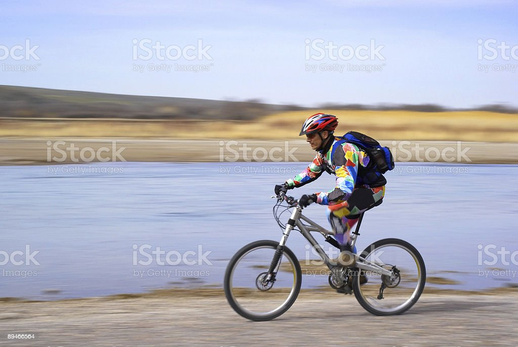 Speed motion biker beside river royalty-free stock photo
