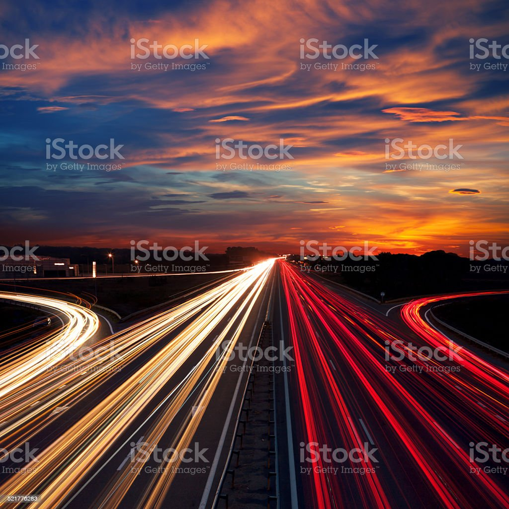 Speed Traffic at Dramatic Sundown Time - light trails stock photo