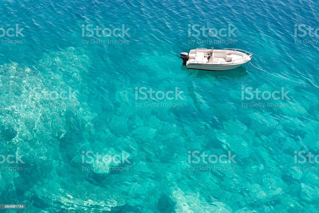 Speedboat anchored in shallow turquoise water stock photo