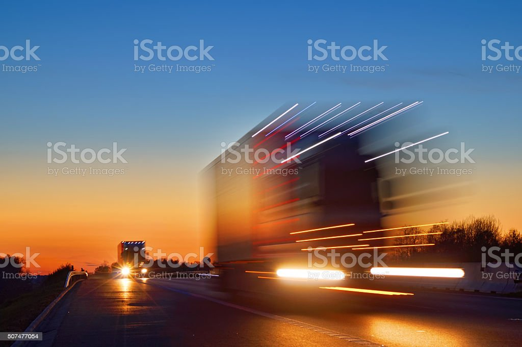 Speeding motion blur oncoming trucks with glowing lights after sunset stock photo