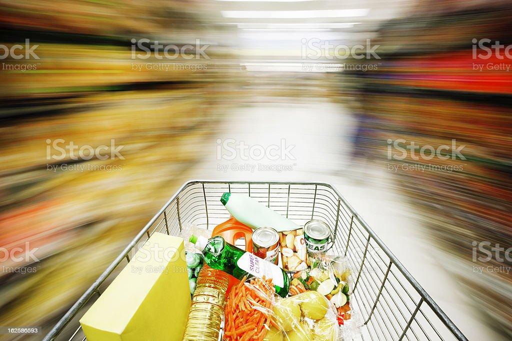 Speeding shopping cart creates motion blur effect on supermarket shelves stock photo