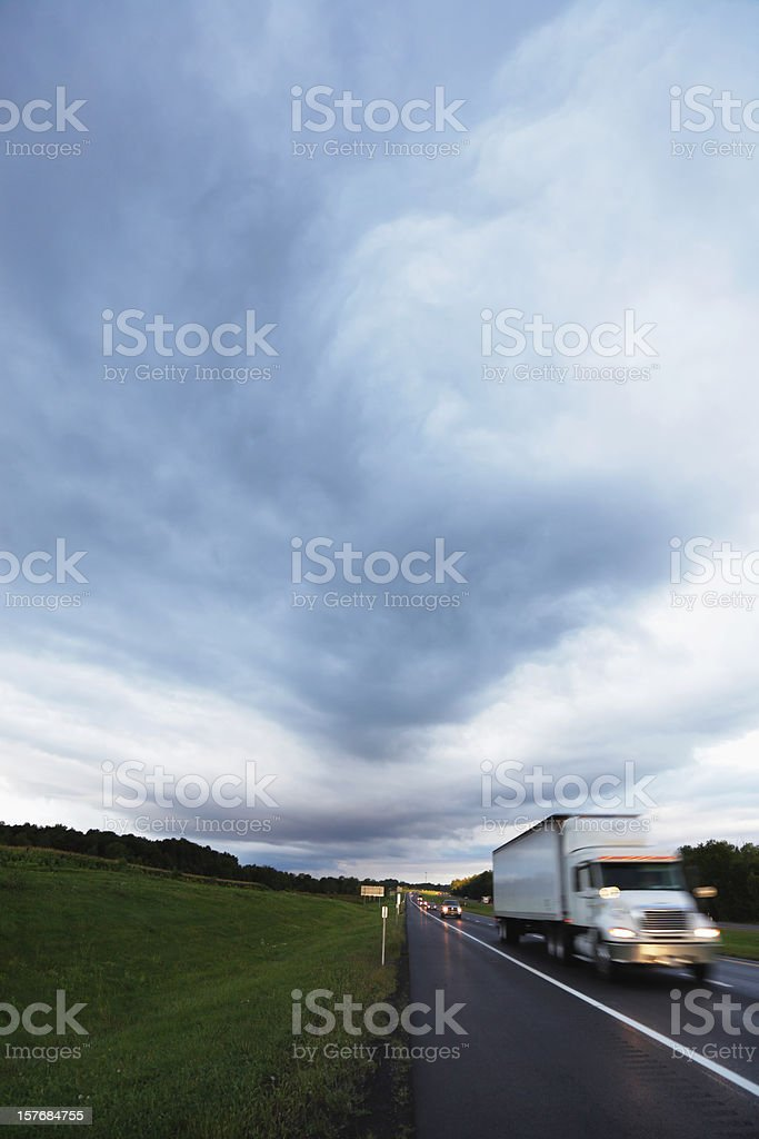 Speeding Trailer Truck on Expressway Under Hurricane Dark Clouds royalty-free stock photo
