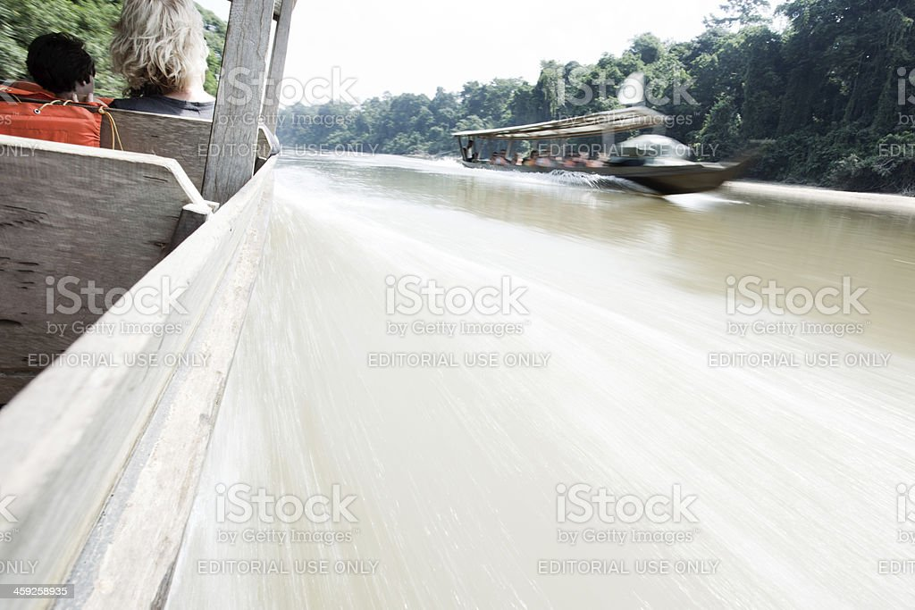 Speeidng on the Taman Negara river with a wooden boat. royalty-free stock photo